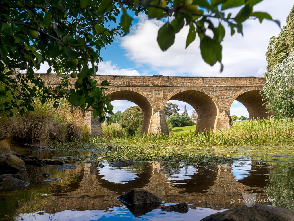 Richmond Bridge, low shot close to water with church spire apearing though an arch.